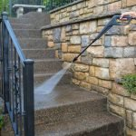 man-pressure-washing-concrete-stairs